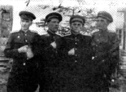 Four early Soviet-era Gulag-camp commandants giving the hidden hand sign for the cameraman
