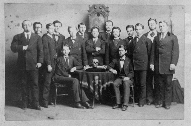 Skull & Bones society In this photo of Skull & Bones secret society members, the man at the far left of the photo is seen displaying the hidden hand sign. Exact date of photo unknown, appears to be around the mid-1800′s.